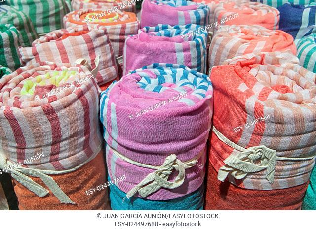 Loads of many rolled colorful light cotton blankets. Closeup