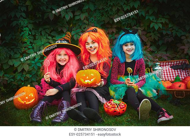 Happy girls with pumpkins and sweets celebrating Halloween outdoors