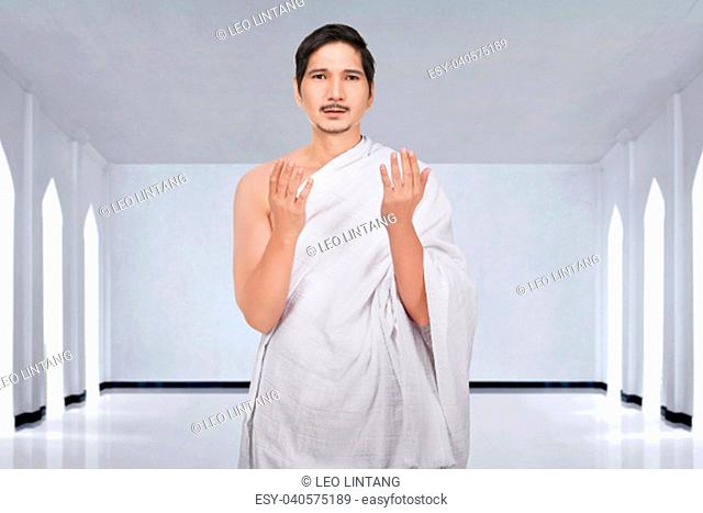 Cheerful asian muslim man in ihram clothes praying on the mosque