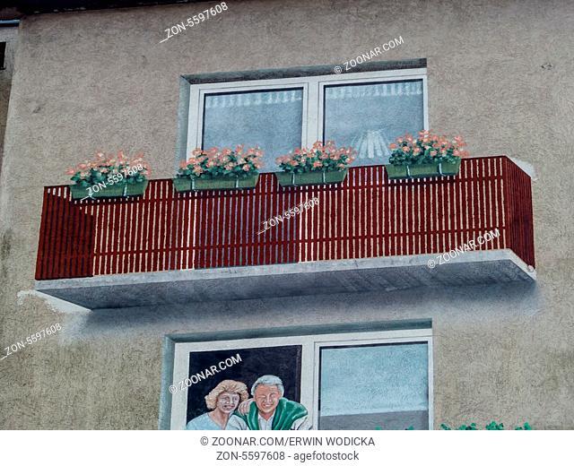 Auf einem Haus wurde ein Balkon mit Farbe aufgemalt. Dreidimensionales Gemälde aus einer Hausfassade