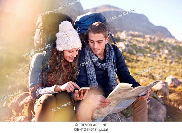 Young couple with backpacks hiking, resting and checking map and smart phone