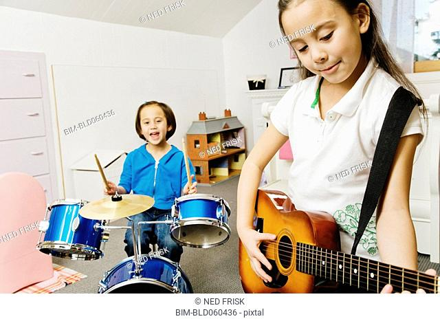 Asian sisters playing drums and guitar
