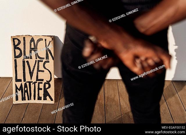 Black Lives Matter sign leaninig on wall, man crossing hands in foreground