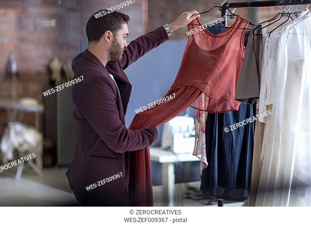 Man looking at dress in boutique