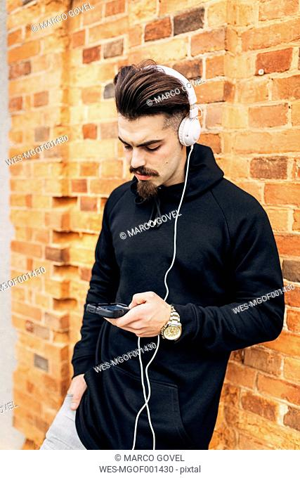 Portrait of young man leaning against brick wall listening music with headphones