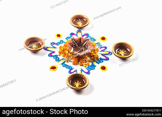 Clay diya lamp lit during diwali festival. Clay Diya on Rangoli. Happy Diwali Greetings Card Design, Indian Hindu Festival of Lights called Diwali