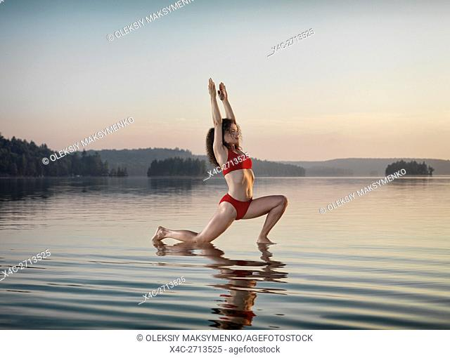Young woman practicing Hatha yoga Low Lunge on a floating platform in water on the lake during misty sunrise in the morning. Yoga Anjaneyasana posture