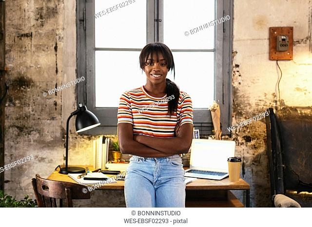 Portrait of smiling young woman standing front of desk in a loft