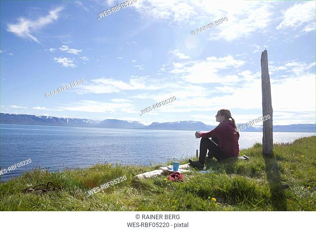 Iceland, hiker resting on a meadow looking at view