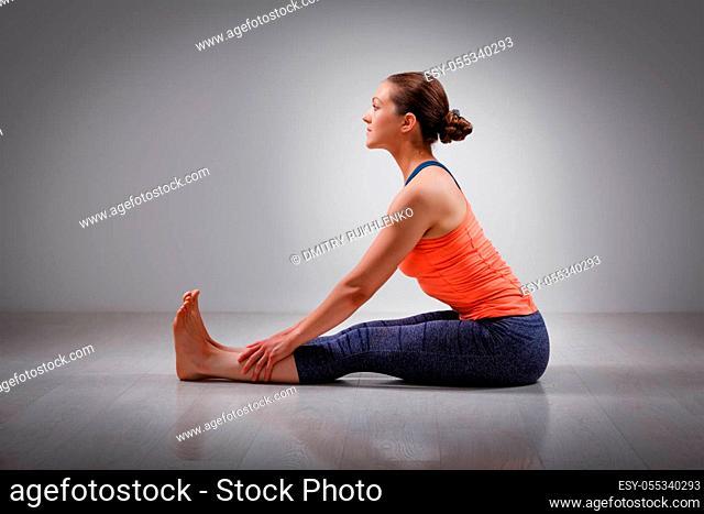Sporty fit woman practices Ashtanga Vinyasa yoga back bending asana Paschimottanasana - seated forward bend beginner variation