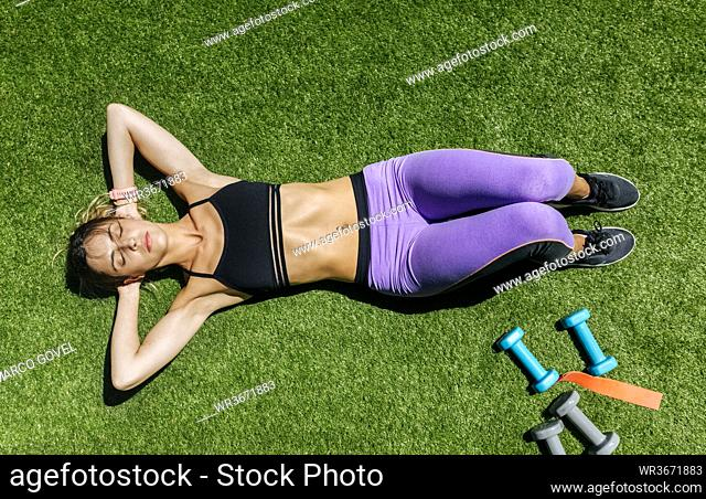 Woman lying on meadow after workout