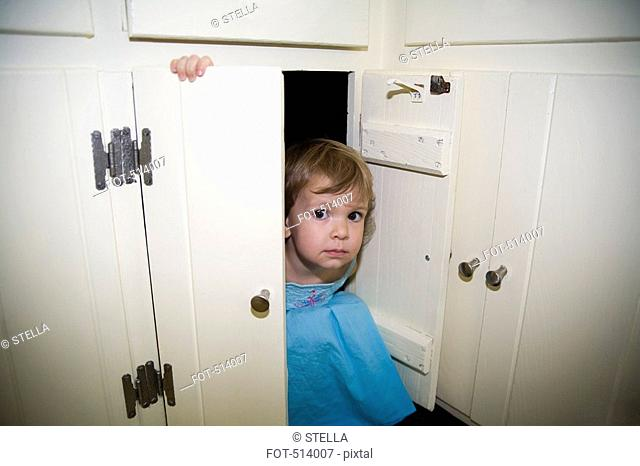 A young girl sitting in a cupboard