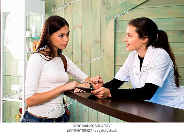 Portrait of female receptionist explaining form to patient in dentist clinic