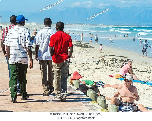 """Four young men trolling on the boardwalk at the seaside on the lookout for """"talent"""". Muizenberg Beach, Cape Town, South Africa"""