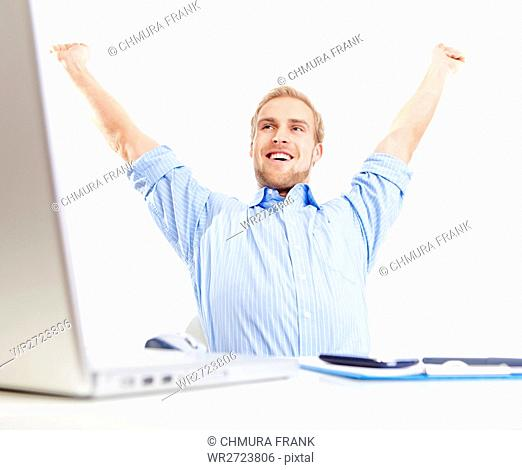 young man at office with his arms outstretched in triumph, smiling