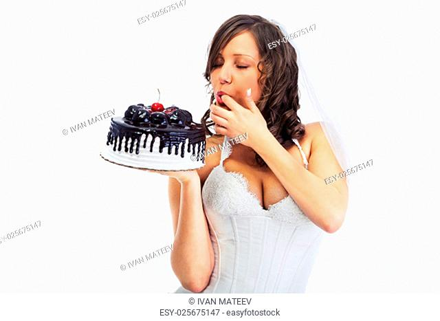 Young bride eating cake isolated on white background