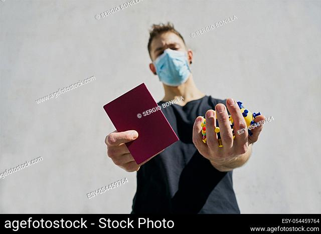 Caucasian male in medical masks with virus mock-ups and passport. Concept of not being able to travel and move around the coronavirus
