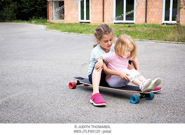 Two sisters sitting on longboard