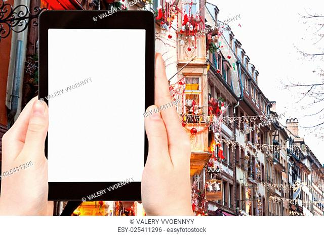 travel concept - tourist photograph urban houses with christmas decoration in Strasbourg, France on tablet pc with cut out screen with blank place for...