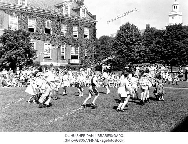 At the end of the school year for a demonstration school at Johns Hopkins University, young boys and girls put on a show in the grass on a sunny day