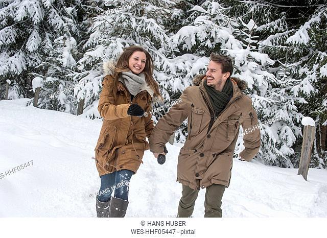 Happy couple walking in winter forest