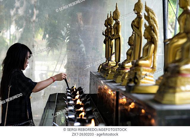 Woman praying in Wat Patum Wanaram Tample. Bangkok. Wat Pathum Wanaram is a Buddhist temple in Bangkok, Thailand. It is located in the district Pathum Wan