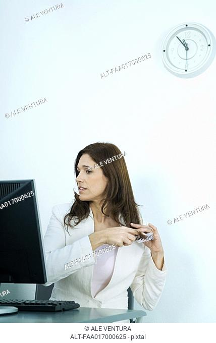 Businesswoman sitting at computer, brushing hair