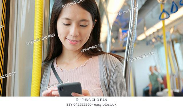 Woman using mobile phone on train