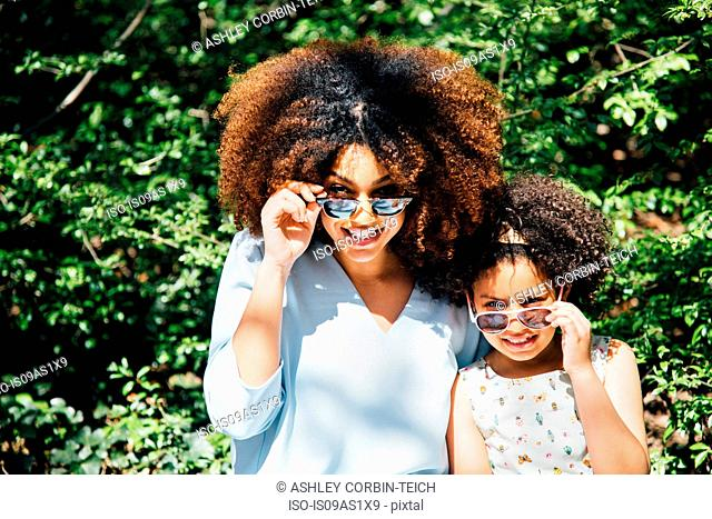 Mother and daughter sitting side by side looking over sunglasses at camera