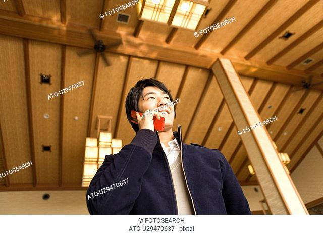 Young man using a mobile phone in a Japanese inn, low angle view, Japan