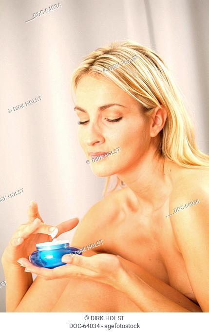 young woman with creme pot is putting skin creme onto her body