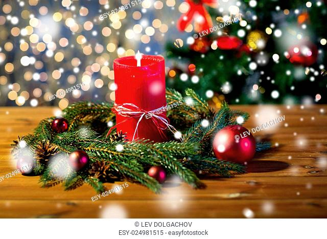 christmas, decoration, holidays and advertisement concept - close up of natural green fir branch wreath with red burning candle on wooden board