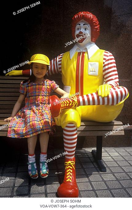 Little girl sits beside Ronald McDonald at McDonald's restaurant in Beijing in Hebei Province, People's Republic of China