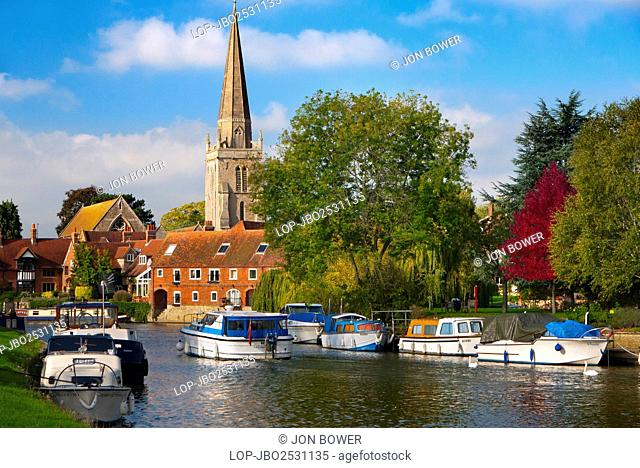 England, Oxfordshire, Abingdon. Leisure boats on the River Thames with St Helen's Church in the background, in Autumn