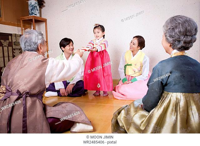 Girl taking new year's cash gifts from her grandfather and other family members watching it