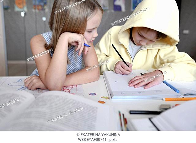 Brother and sister sitting at table at home doing homework together