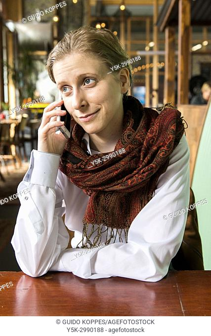 Tilburg, Netherlands. Caucasian blonde woman making a mobile phonecall while sitting at Cafe RAW's table. Friendships are often maintained at a distance