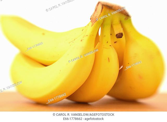 Bunch of bananas, laying on wooden cutting board on white background Shot with LensBaby for selective focus