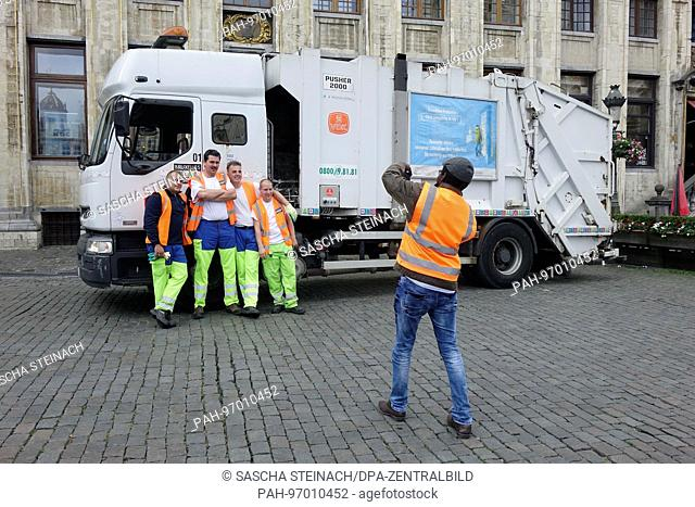 City cleaning staff pose for a photograph in front of their vehicle, which is parked outside the house of the Dukes of Brabant (Maison des Ducs de Brabant) at...