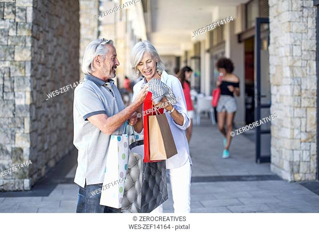 Senior couple taking a city break, going on a shopping spree