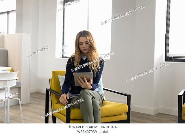 Front view of a young Caucasian woman sitting in an armchair using a tablet computer in the lounge area of a creative business