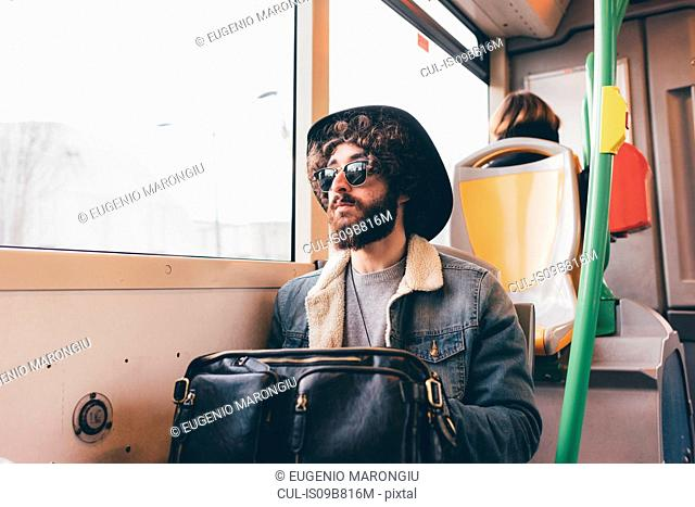 Young man sitting on subway train