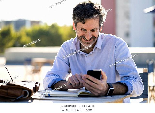 Smiling mature man sitting at outdoor table with cell phone and notebook