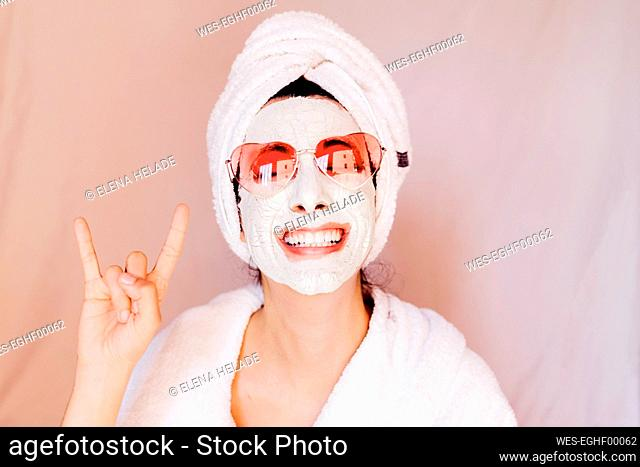 Happy young woman with beauty face mask showing horn sign against peach background