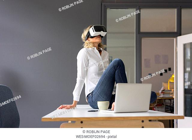 Young businesswoman sitting on desk in office wearing VR glasses