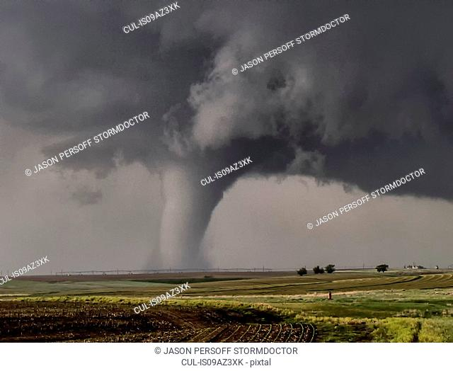 A large cone tornado touches down over the open prairie