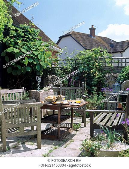 Wooden benches and table set for lunch on sunny paved patio in country garden