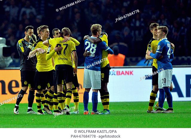 Berlin's Mitchell Weiser (r) and Fabian Lustenberger (c) congratulating the team of Dortmund after the German DFBCup semi final soccer match between Hertha...