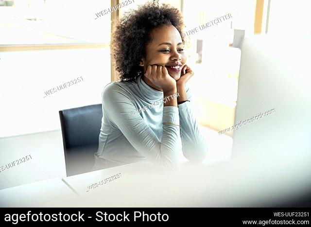 Smiling female professional with hand on chin looking at computer in office