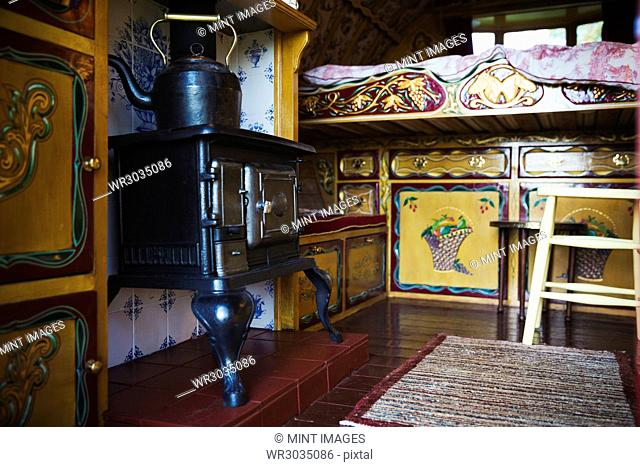A cast iron stove with large metal kettle, a mantlepiece and storage cupboards and raised bed, the interior of a gypsy caravan